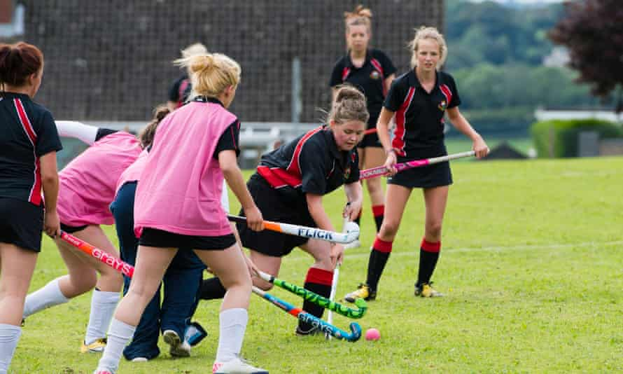 Teenage girls playing hockey outdoors at a secondary comprehensive school in Wales