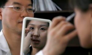 "Korean plastic surgeon Kim Byung-gun demonstrates ""double eyelid"" surgery for a patient during a consulting session in his clinic in Shanghai in 2007."
