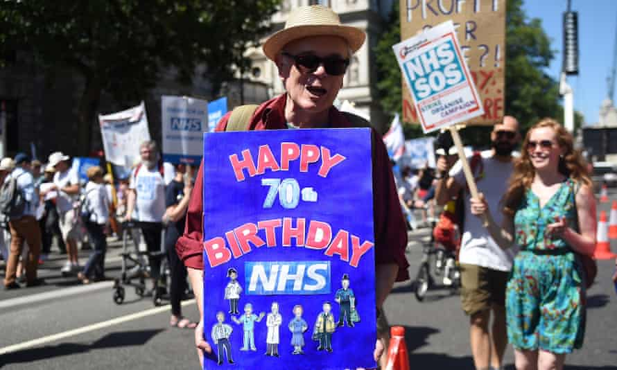 A man with a birthday placard as thousands of people march to mark 70 years of the NHS