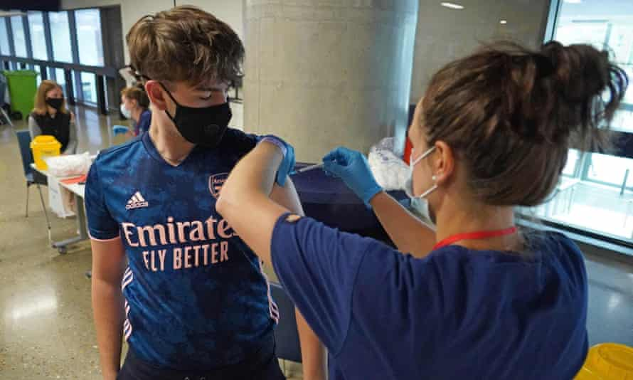 An 18-year-old boy is vaccinated at Tottenham Hotspur's stadium in London.