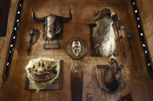 The heads of creatures from various Star Wars films are mounted on the wall of the Dok-Ondar's Den of Antiquities store
