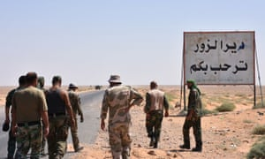 Syrian government troops stand beside a 'Welcome to Deir ez-Zor' sign.