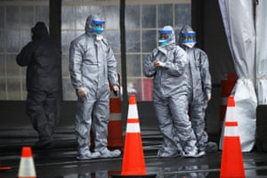 Workers in protective gear operate a drive-through mobile testing center in New Rochelle, New York.
