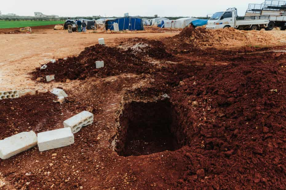 A freshly dug grave and nearby, tents set up by people fleeing a pro-government forces offensive, in a cemetery near the Syria-Turkey border.