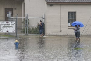 People wait in the flood waters by the Farrington Baptist Church off of highway 69 North on 19 September in Houston, Texas.