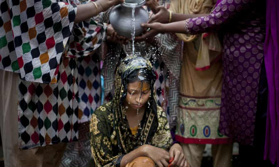 A 15-year-old girl is bathed on the day of her wedding to a man more than twice her age in Manikganj, Bangladesh