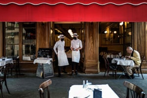 Waiters stand at the entrance of a Bouchon Lyonnais, a typical local restaurant in Lyon