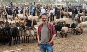 David Baddiel standing with the goats touring Kashgar Sunday livestock market, Xinjiang Region, China.