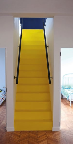 Yellow stairs lead down to the bedrooms.
