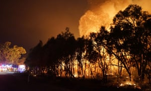 Firefighters watch as a blaze moves through Deepwater National Park in Queensland