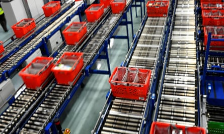 Conveyer belts transport crates filled with packed bags inside the Ocado customer fulfilment centre in Hatfield