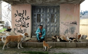Amman, Jordan. Ali sarsour, an upholsterer, plays with his dog and cats as he wears one of his suits near his home