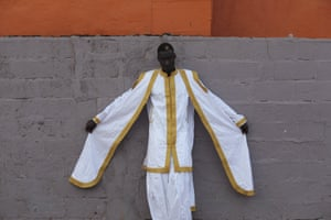 Model Awuah in white suit trimmed with gold