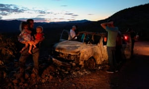 Members of the LeBarón family look at the burned car where some of the nine murdered members of the family were killed during the ambush.