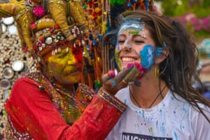 A tourist in Pushkar has her face covered in paint