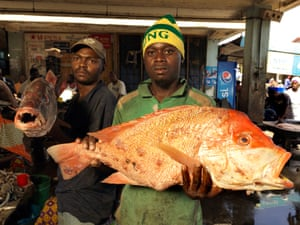 Abdul, 23, holds a large red snapper