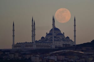 The supermoon rises above the Camlica Mosque in Istanbul, Turkey.
