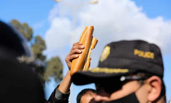 A demonstrator holds up loaves of bread at a protest in Tunis on Tuesday.