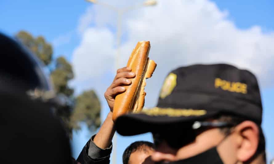 A protest holds up bread at an anti-government demonstration in Tunis. The country's political upheavals have added to its debt woes.