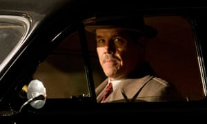 Josh Brolin in 1950s costume sits in a car in darkness, lit by oncoming headlights