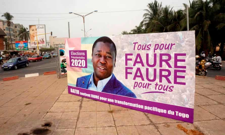 Motorists drive past a campaign billboard in Lomé bearing the image of President Faure Gnassingbé