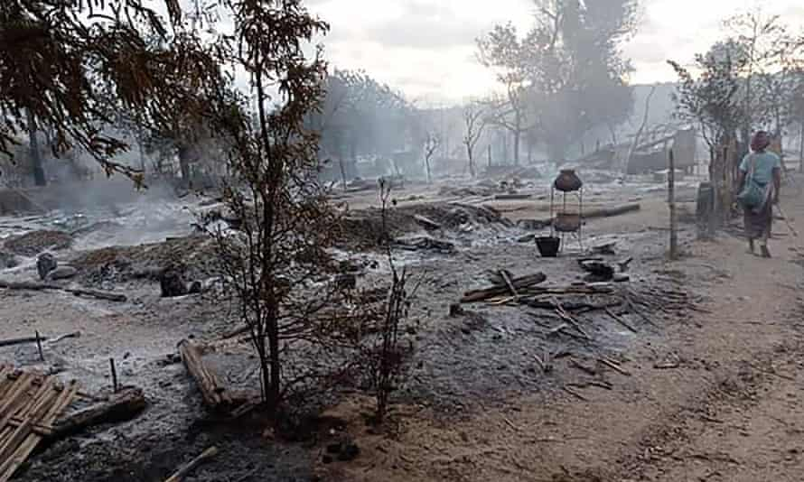 A woman walking past the remains of houses after they were burnt in Kin Ma village in Myanmar