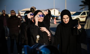 People watch the last solar eclipse of the year in Manama, Bahrain
