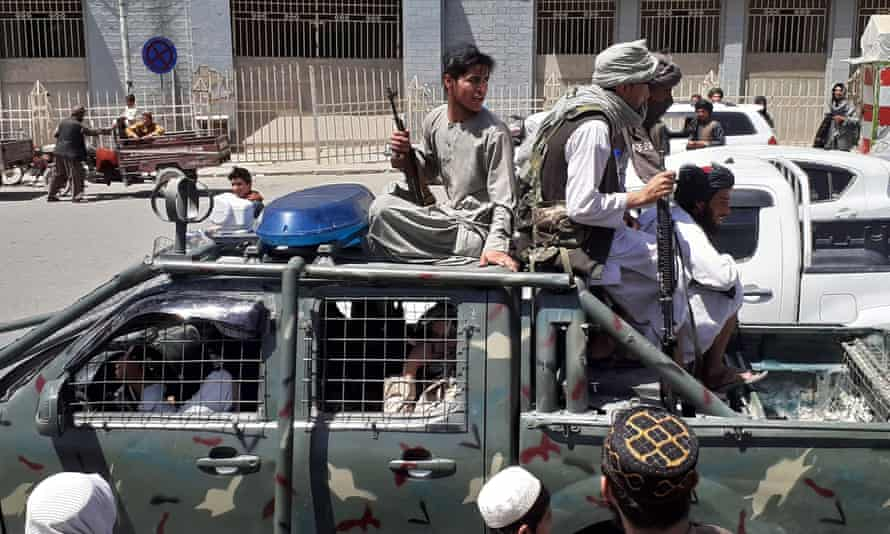 Taliban fighters drive through Kandahar in a captured military vehicle