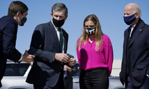 An aide asks Governor Roy Cooper to step back as he greets Joe Biden and his granddaughter Finnegan Biden in Morrisville, North Carolina on Sunday.