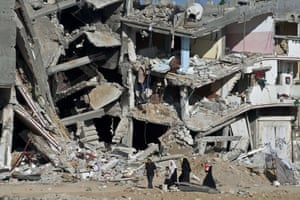 Shejaiya, 2014 A Palestinian family walks past the collapsed remains of a building
