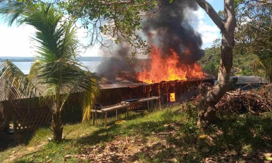 Houses burn in a Munduruku village after an attack by wildcat miners in the Brazilian state of Roraima.
