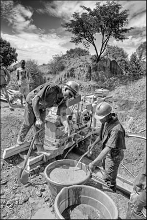 Miners work the ore crushing machine and pan and wash for specks of gold at the Tiira mine