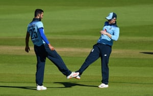 England's Saqib Mahmood touches his foot with Eoin Morgan (R) after taking the wicket of Ireland's Barry McCarthy.