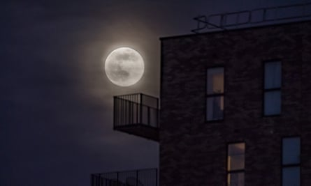 A supermoon rises behind clouds above an apartment block on 7 April 2020 in Manchester, UK