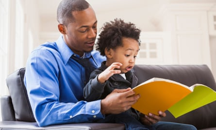 Father and son reading on sofa