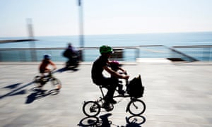 A man rides a bicycle with a child on a seaside promenade in Barcelona as children under the age of 14 are allowed to leave their homes for the first time in weeks.