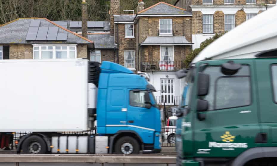 An English flag hangs from the balcony of a house in Dover, as cross-Channel lorries pass.