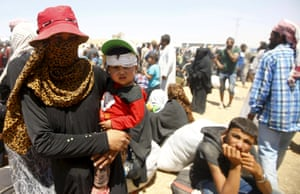 Syrian refugees wait for transportation after crossing into Turkey from the Syrian town of Tal Abyad