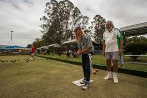 Locals Charlie and Hip play bowls together early on Sunday morning while they enjoy a beer, as musicians play at the bowls club