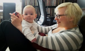 Keza plays video games with her baby son.
