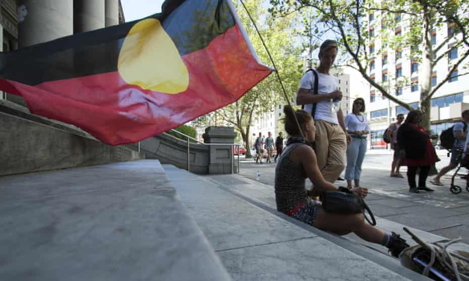 A protester sits with the Aboriginal flag outside South Australia parliament in Adelaide.