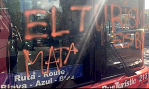 Four hooded men attacked a city tourist bus in Barcelona and spray-painted 'Tourism kills neighbourhoods' on the windscreen as they shouted abuse at the passengers.