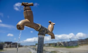 A communal tap runs as people collect water in a settlement near Cape Town, South Africa. On 11 May, the city is due to be the first in the world to turn off the water taps.