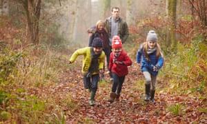 a Family Walking Through Winter Woodland Having Fun