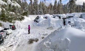 A photo from video shows people attempting to clear cars buried in the parking lot of the showed-in Montecito Sequoia Lodge in Kings Canyon national park in California's Sierra Nevada on 6 February.