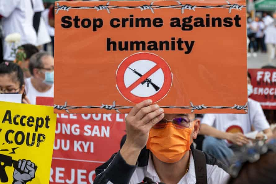 A man holding a sign reading 'Stop crime against humanity' at a protest against the Myanmar coup in Taipei, Taiwan