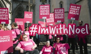 Campaigners from Dignity in Dying and supporters of Noel Conway, who has motor neurone disease, carry banners with slogans such as 'Give me choice over my death' and '#ImwithNoel'.