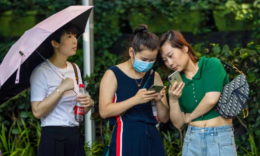 Young people use their phones in Shanghai, China.