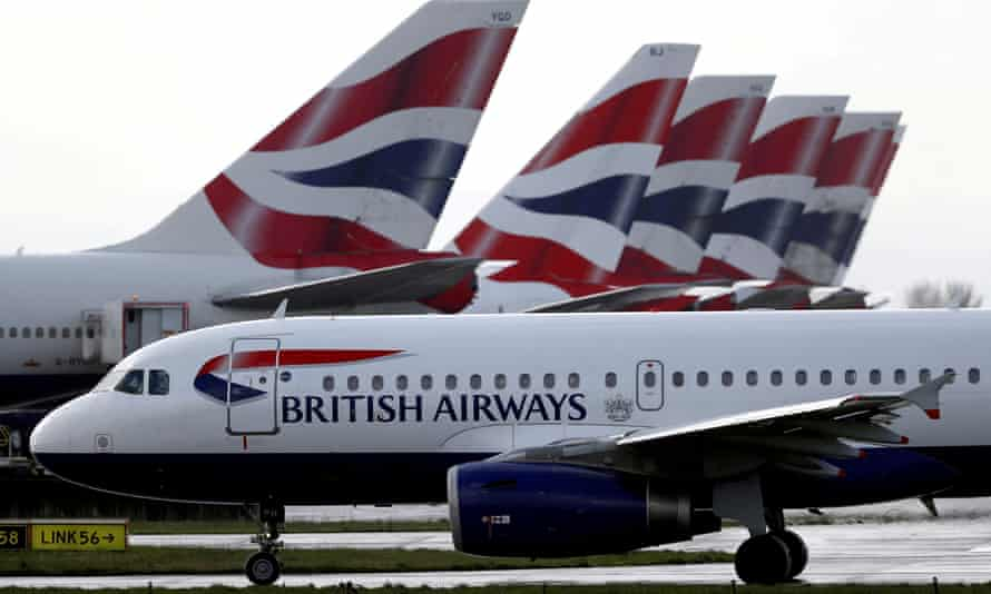 A British Airways plane taxis past tail fins of parked aircraft at Heathrow