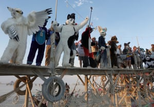 People dressed as furry animals perform on the art installation The Pier